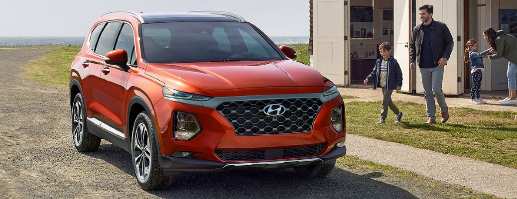Red 2020 Hyundai Santa Fe parked by a seaside home
