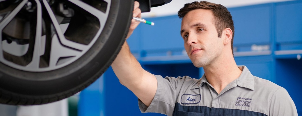Hyundai mechanic works happily on a wheel