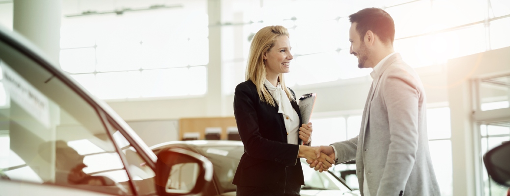 Man shakes woman's hand after trading in his vehicle without purchasing a new one