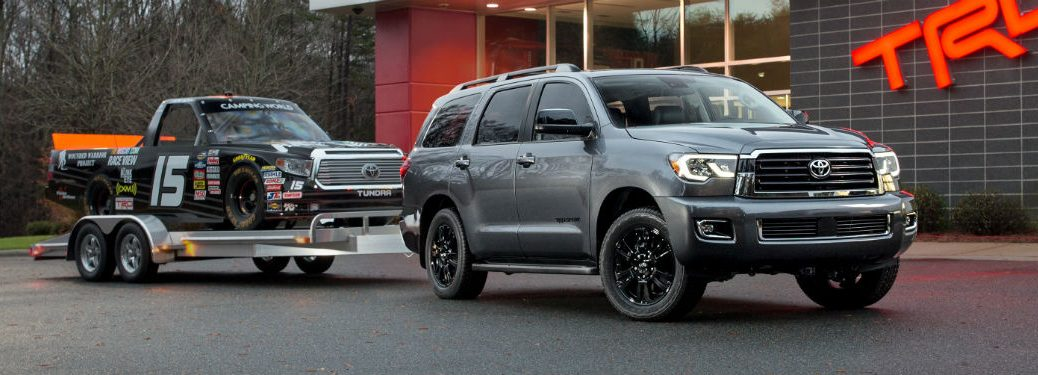 Passenger side exterior view of a gray 2019 Toyota Sequoia towing a race truck on a trailer