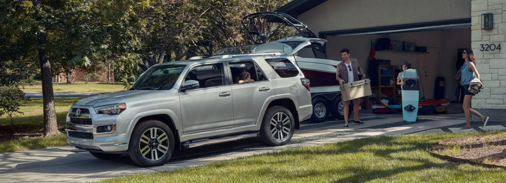 Driver side exterior view of a gray 2019 Toyota 4Runner being loaded by a family with cargo for a vacation