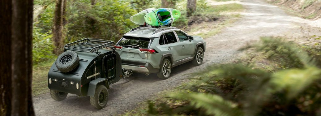 Rear passenger side exterior view of a gray 2019 Toyota Rav4 towing a small trailer