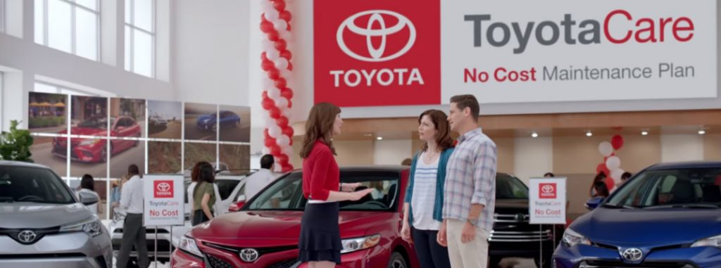 An image of three people in a dealership in front of a ToyotaCare sign