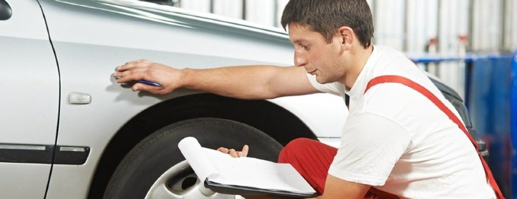 man inspecting a car with a sheet of paper