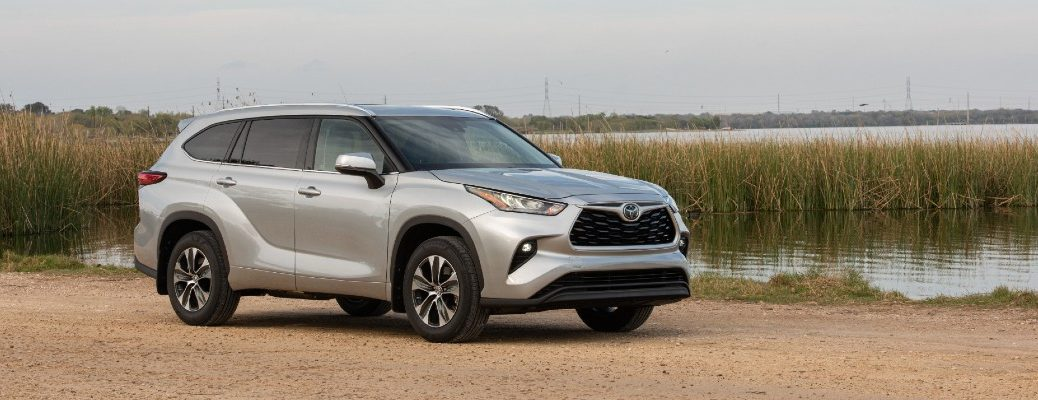 A right profile photo of the 2020 Toyota Highlander parked by a marsh.