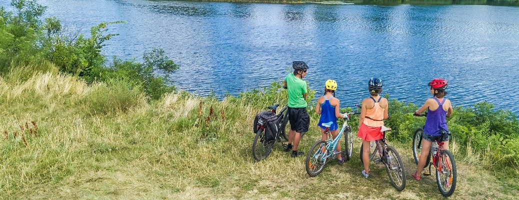 A stock photo of a family on bikes visiting a lake.