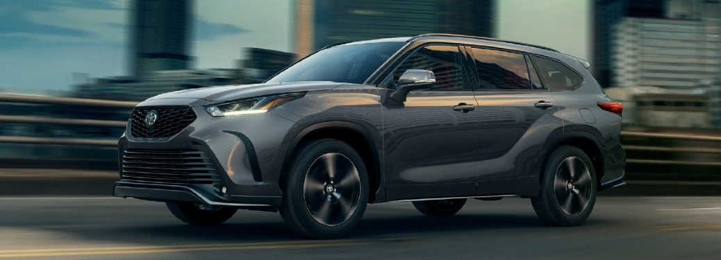 Front driver angle of a grey 2021 Toyota Highlander driving on a road