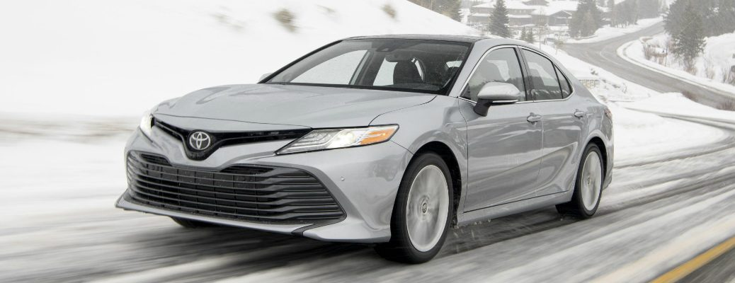 Silver 2020 Toyota Camry AWD driving on a snowy road
