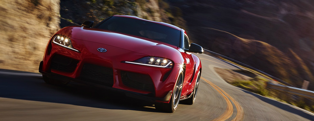 Red 2020 Toyota GR Supra driving on a curvy mountain road