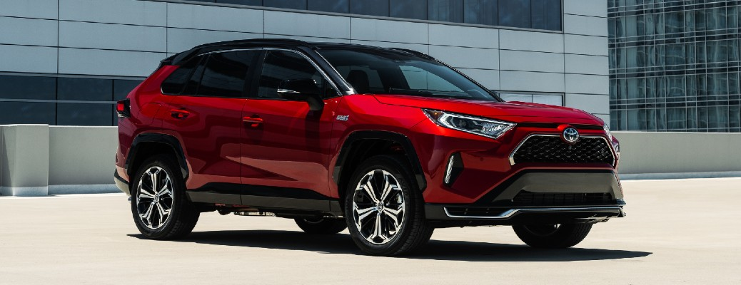 Red 2021 Toyota RAV4 Prime parked in front of a large building