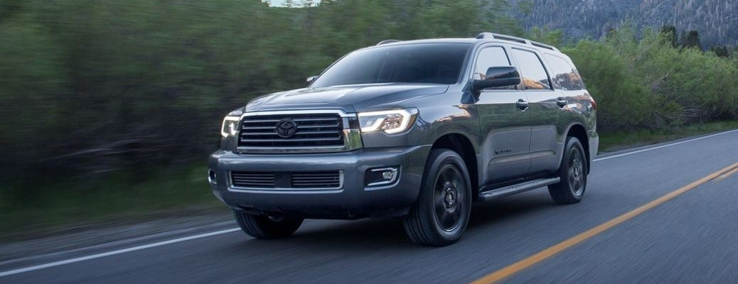 2021 Toyota Sequoia driving down a road with trees in the background