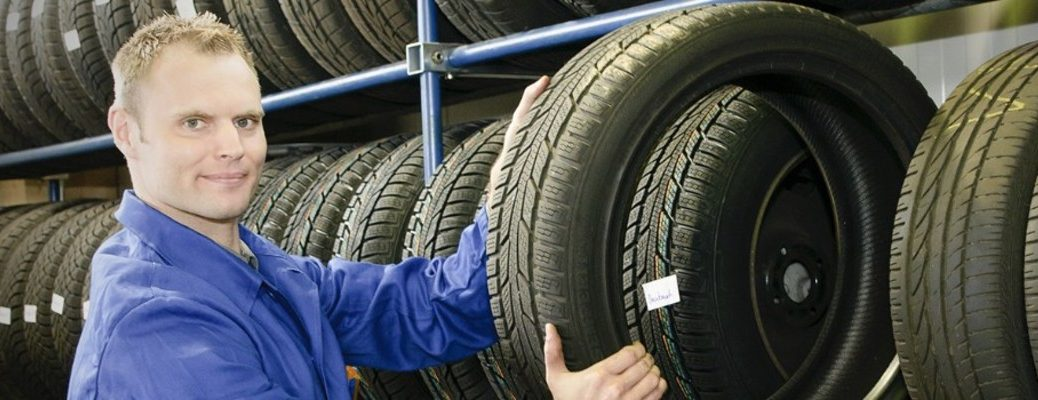 a man holding a tire by a tire rack