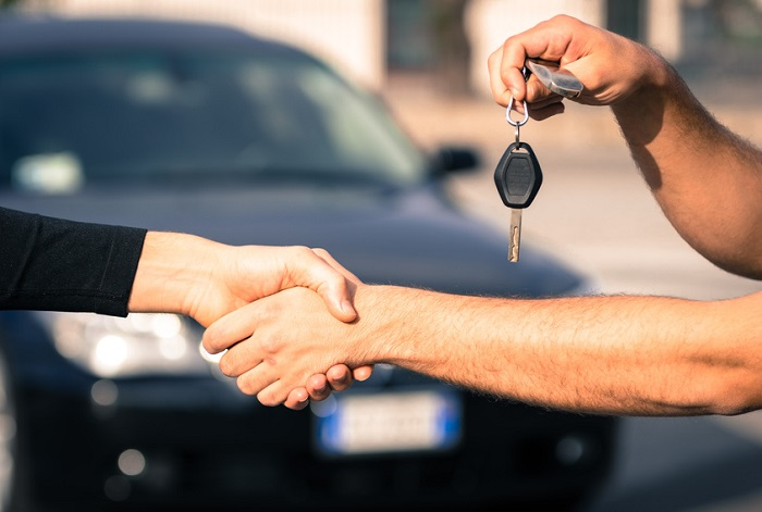 Image of two hands shaking in front of a black sedan.