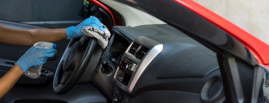 gloved hands cleaning steering wheel with spray bottle and rag
