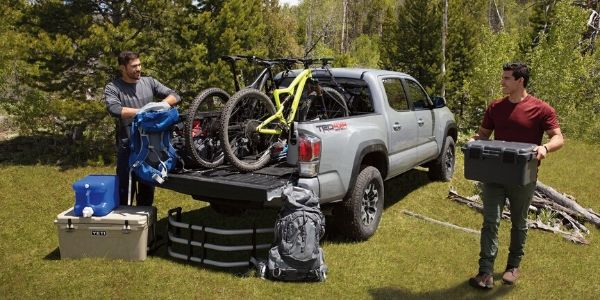 Two Men Unloading Cargo From a 2020 Toyota Tacoma