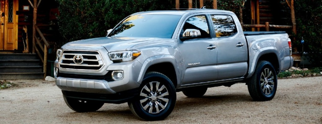 A silver-colored 2021 Toyota Tacoma parked outside near a structure