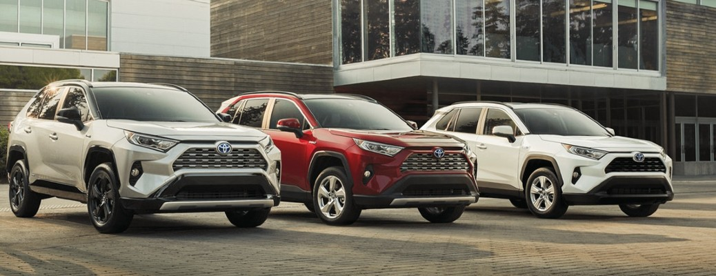 Three 2021 Toyota RAV4 vehicles parked outside a building