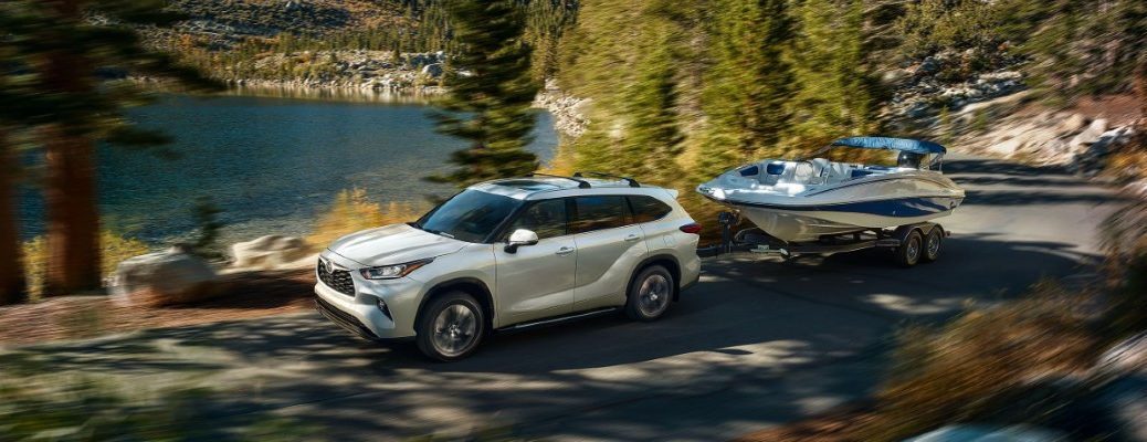 2020 Toyota Highlander towing a boat by a lake