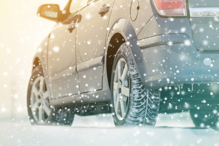 Close-up of the tires of a car driving in the snow