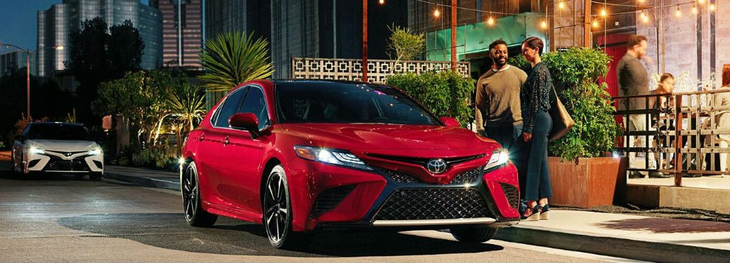 2020 Toyota Camry red exterior front fascia passenger side parked couple by driver side