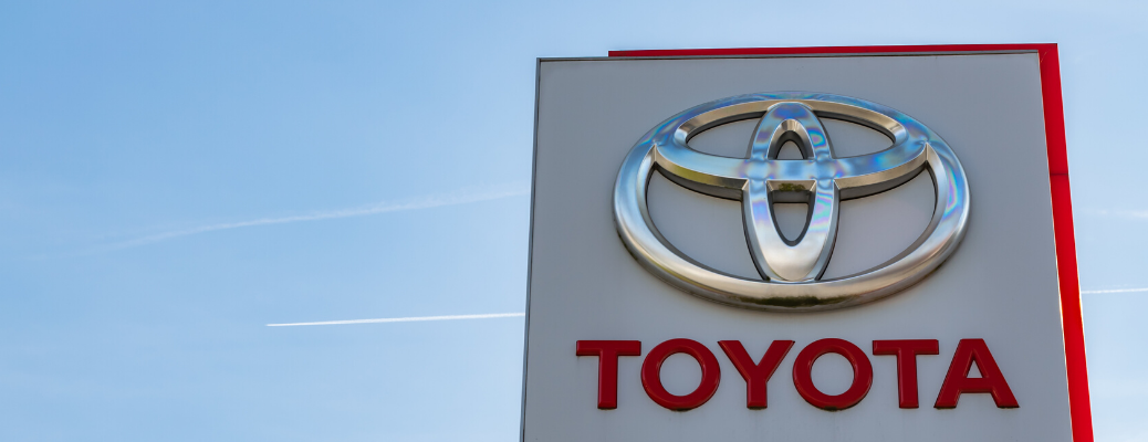 Toyota dealership sign with brand logo on a blue sky background