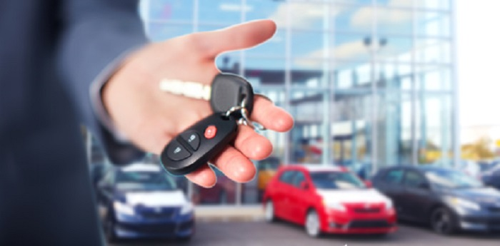 Hand with car keys at a dealership
