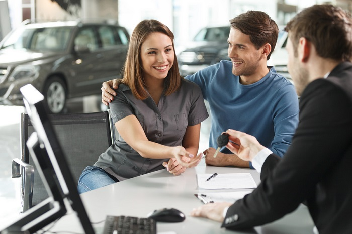 Couple discussing car warranties with salesperson