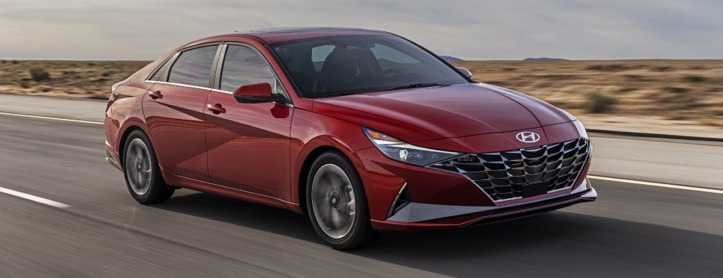 2021 Hyundai Elantra redesign exterior shot with red paint color driving down a desert highway