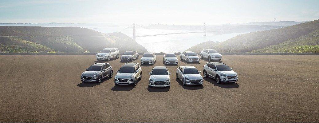 Hyundai Model line up in silver paint color parked on a dirt plain looking out on a bright sky and river bridge for Hyundai Assurance job protection banner image