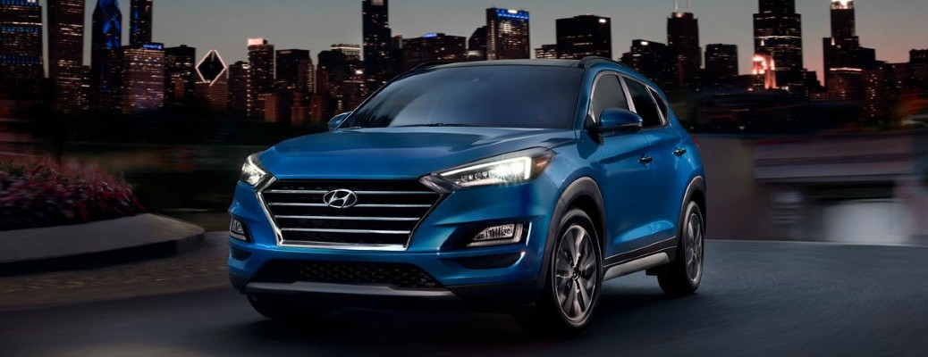 The front exterior view of a blue 2021 Hyundai Tucson with its light on at night.