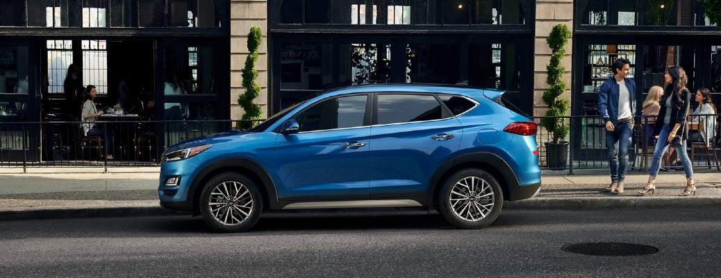 The side view of a blue 2021 Hyundai Tucson parked on the side of a city street.