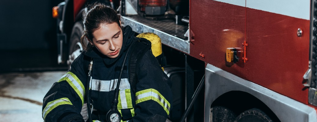 A tired female worker sitting next to a fire truck