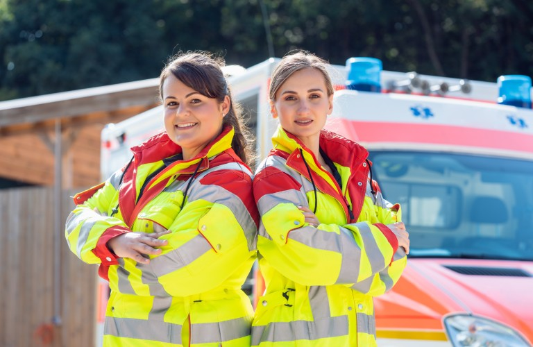 A female doctor and paramedic standing back-to-back in front of an ambulance.
