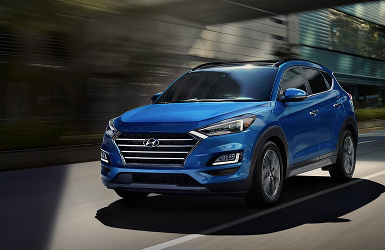 A side and front image of a blue 2020 Hyundai Tucson driving quickly down an open road.