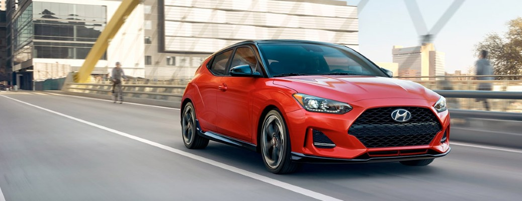 An orange 2020 Hyundai Veloster Turbo driving down a city road.