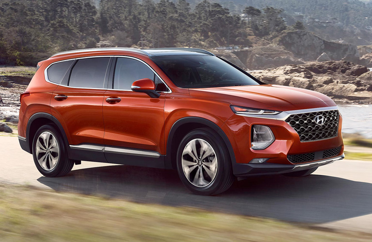 The front and side view of an orange 2020 Hyundai Santa Fe driving down a dirt road.