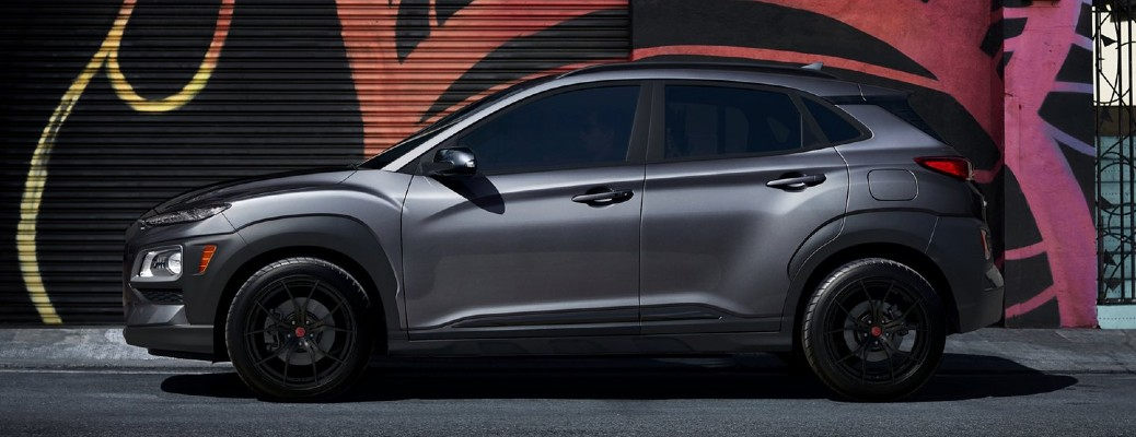 The side view of a black 2021 Hyundai Kona Night Edition against a mural wall.