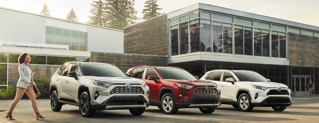 A photo of three Toyota RAV4 models lined up in front of a home.