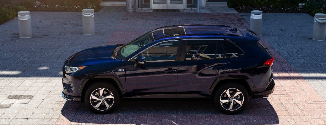 A left profile photo of the 2021 Toyota RAV4 Prime parked in front of a building.
