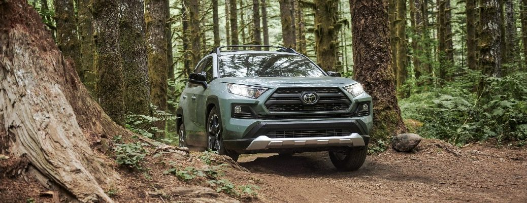 A photo of the 2021 Toyota RAV4 driving through the woods.