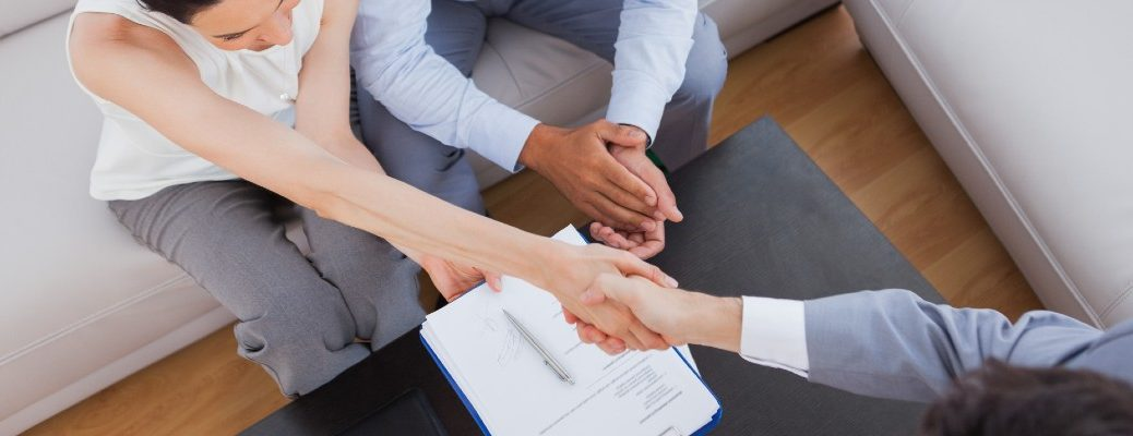 A stock photo of people signing paperwork.
