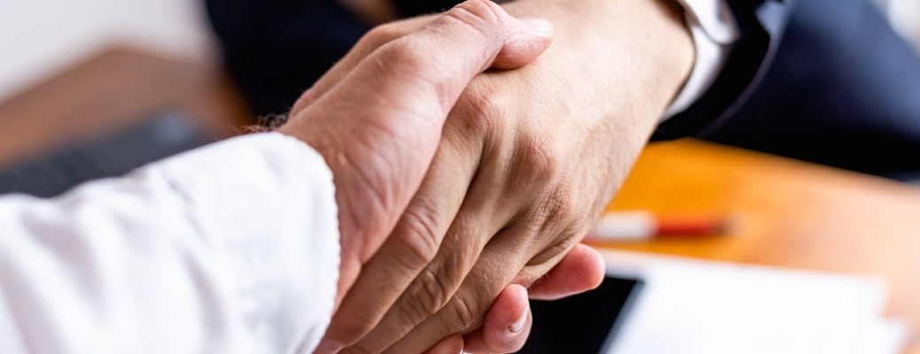 Two people shaking hands after completing a deal in a stock photo.