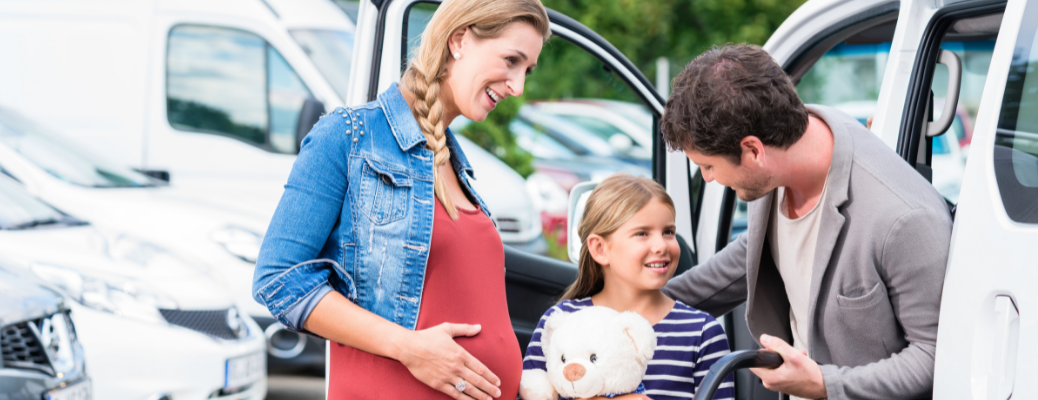 A man and woman with a kid in front of a car