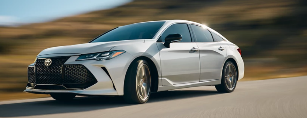 2022 Toyota Avalon passing from a road near hills