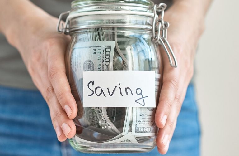 """Image of a jar filled with cash with """"saving"""" written on the jar"""