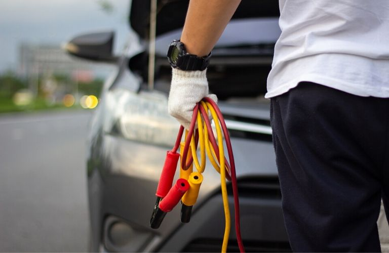 Image of a person carrying jumper cables to a stranded car