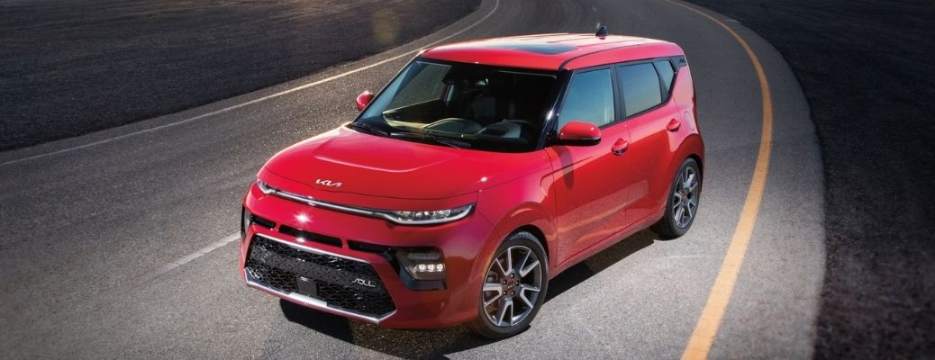 Space Red 2022 Kia Soul on a road. Learn about the fuel economy rating