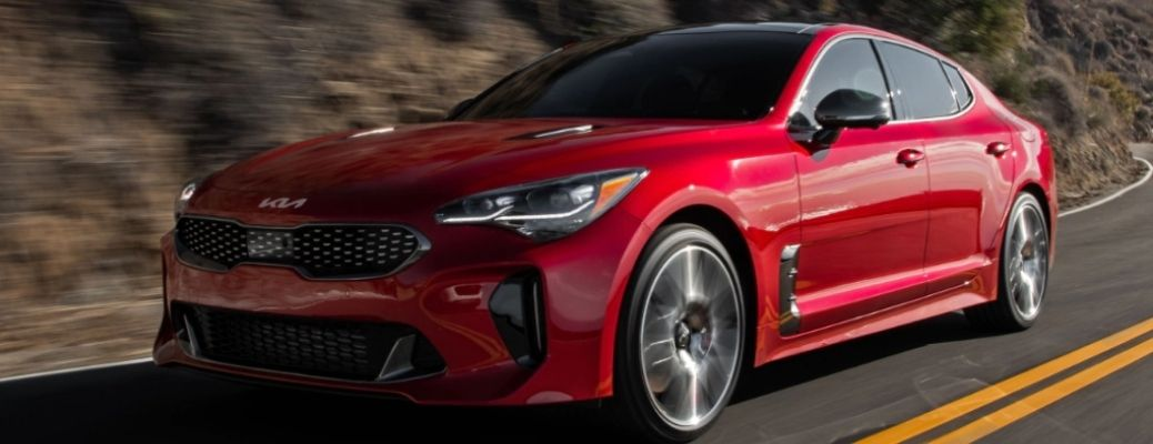 Red 2022 Kia Stinger cruising on a road. What are the safety features?