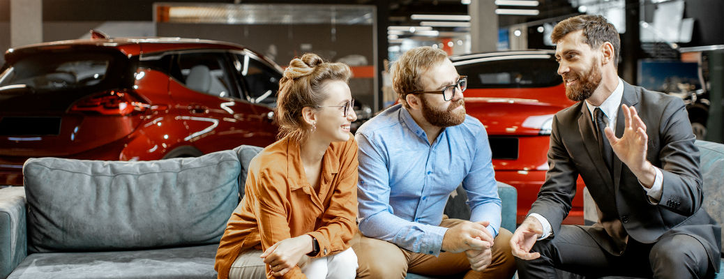 Man and woman talking with sales manager at dealership