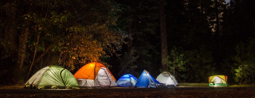 group of six tents with lights on in forest at night